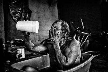 A jobless man bathes in a bucket.  Lanare, California.