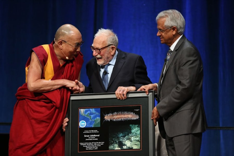 The Dalai Lama accepts a framed image of a Sirsoe dalailamai, a deep-sea worm named after him in honor of his 80th birthday. He is photographed with Scripps geophysicist Walter Munk and climate and atmospheric scientist Veerabhadran Ramanathan. Courtesy Scripps Institution of Oceanography, UC San Diego.
