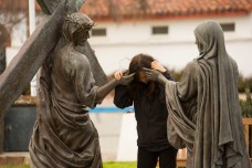 A visitor to Mission San Luís Rey de Francia prays with statues of Jesus Christ and the Virgin Mary. (Contemporary Pilgrimage site.)