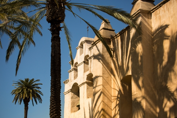 Non-native palm trees decorate the exterior façade of Mission San Gabriel Arcángel, contributing to the romanticized notions of California's Spanish past.